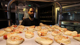 Baker placing tray of pastry in an oven Footage