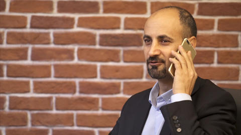 Business man with white smartphone speaks and smiles - Brick wall background Footage