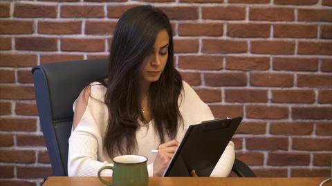 Business woman taking note in a notepad at office and drink coffee - Brick wall Footage