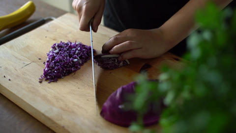Woman chopping fresh red cabbage on a wooden table in kitchen Footage