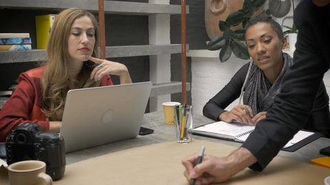 A man writes an idea on paper with his female co workers at a strategy meeting i GIF
