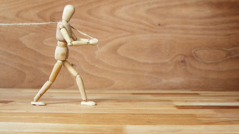 Wooden figurine pulling a rope on wooden floor Footage