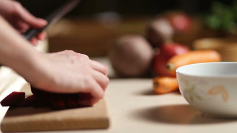 Woman's hands slicing beet on wooden cutting board Footage