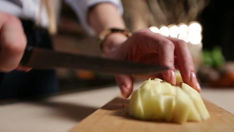 Female hand slicing peeled apple on cutting board Footage