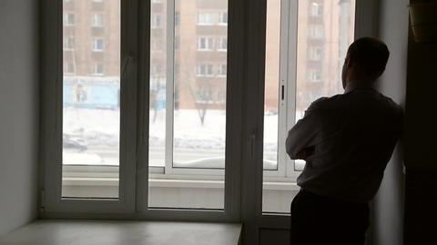 A man stands near window Footage