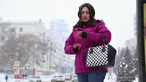 A girl stands at the bus stop in winter Footage