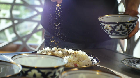 Closeup Cook Pours Spice Herbs Over Rice on Plate Footage