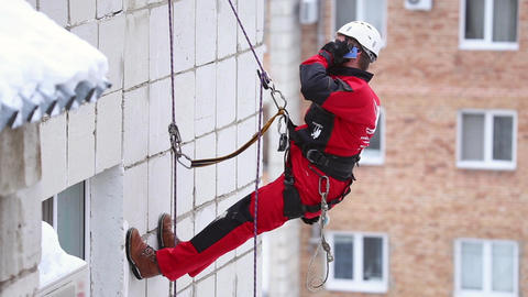 Industrial climber talking on a mobile phone Footage