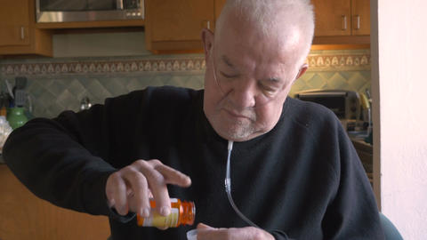 An attractive, aging, senior man getting pills out of his prescription bottle we Footage