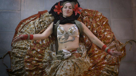 A beautiful woman belly dancer laying of the floor with a large skirt dancing sh Footage