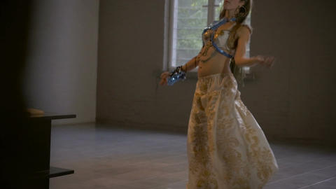 A slider shot revealing an attractive belly dancer dancing in traditional arabic Footage