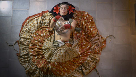 A woman belly dancer in a colorful costume laying on the floor dancing shot from Footage