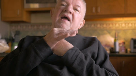 An elderly senior man talking while sitting next to his pills and medication in  Footage