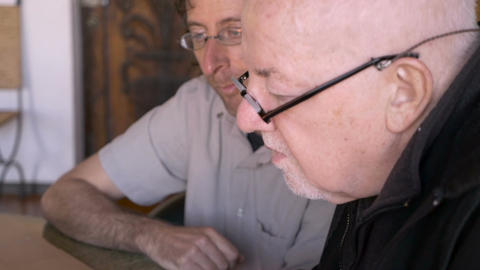 A man points to a computer while an elderly senior man uses the trackpad on his  Footage
