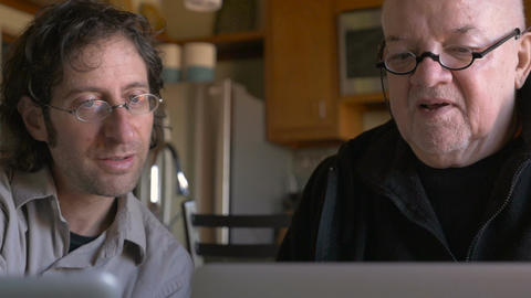 An older senior father and son sit next to each other and work on their laptops  Footage