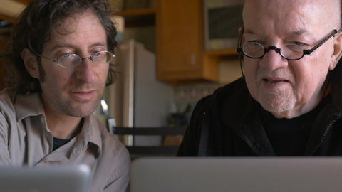 A younger man is teaching an elderly senior man how to use a laptop - dolly shot Footage