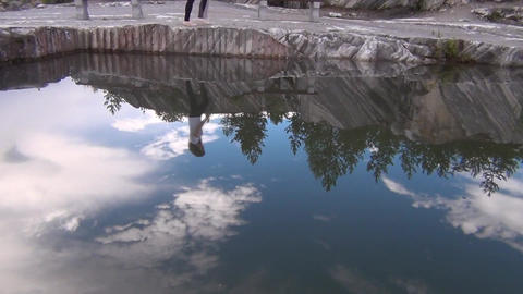 Reflection on water of a walking girl Footage