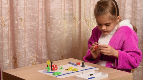 Girl sculpts crafts from plasticine sitting at a table on the other side of the  Footage