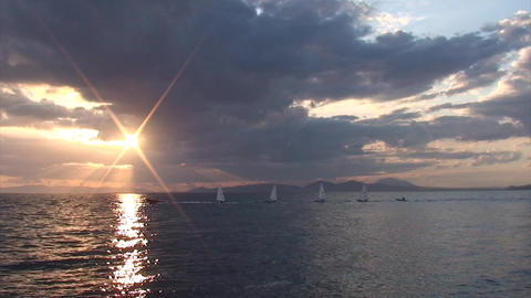 Inflatable boat is towing small sailboats during sunset Footage