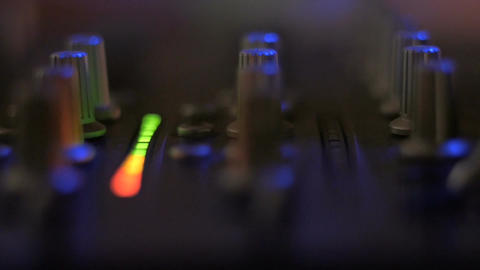 Extreme closeup of knobs and led lights on a DJ turntable inside a night club Footage