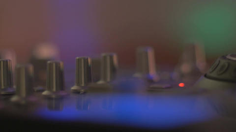 Close up slider of a DJ mixing turntable with flashing led lights in a dance clu Footage