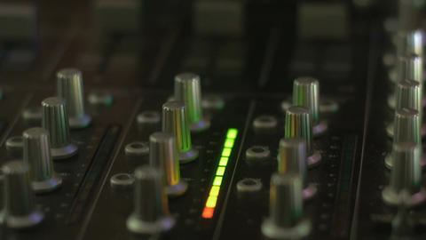 Push in of a hand moving a slider up to it's full level on a DJ mixing board Footage