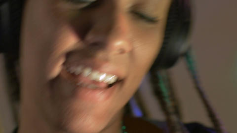 A beautiful mixed racial woman wearing headphones dancing and smiling with flash Footage