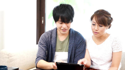 Couple using a mobile tablet device pan Footage