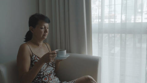 Woman drinking coffee near the window Footage