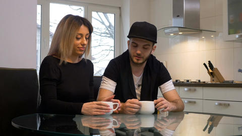 Man and woman having a coffee and chatting at home in the kitchen in the morning Footage