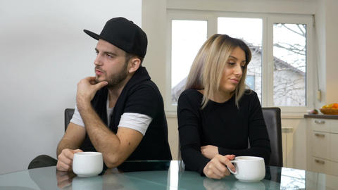 Upset sad couple drinking coffee after a fight sitting in the kitchen at home Footage