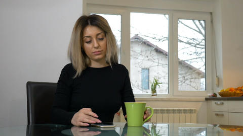 Woman sitting in the kitchen and scrolling the phone while drinking coffee Footage