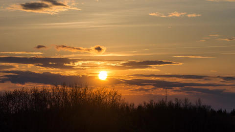 Orange sun setting behind clouds and trees Footage