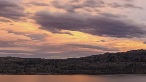 Time lapse pastel colored sunset clouds over lake Footage