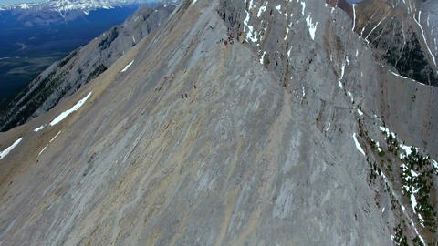 Aerial: Orbit around hikers preparing to follow steep mountain ridgeline Footage