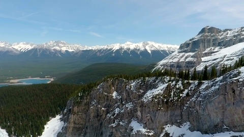 Aerial: Rising over mountain ridge with view of forest and snow capped peaks Footage