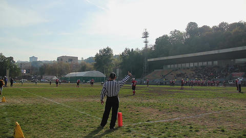 Field official showing thumbs-up to players and referees on gridiron during game Footage