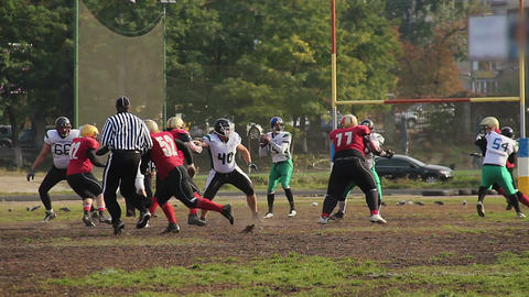 Exciting football game, cornerback attacking player with a ball, teams running Archivo