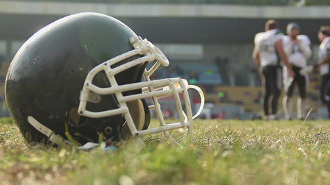 Helmet lying on football pitch, team training at gridiron sports school, hobby Live Action