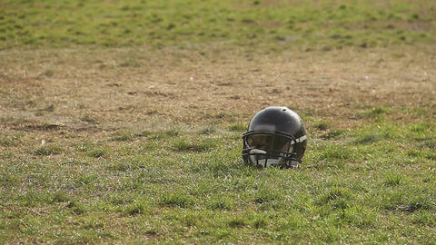 Black football helmet lying on pitch, professional sports, outdoor activities Footage