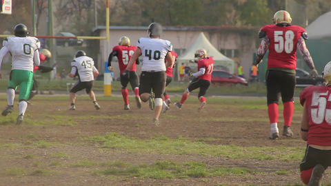 Quarterback running to end-zone and gets tackled, football game in small town Footage