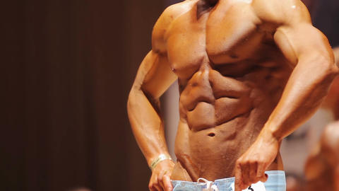 Bodybuilder posing on stage at sports competition, showing perfect male body Footage