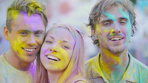 Excited faces of beautiful young people covered in colors smiling at camera Footage