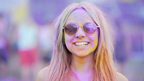 Girl in sunglasses covered in colorful dyes smiling, blowing air kiss to camera Footage