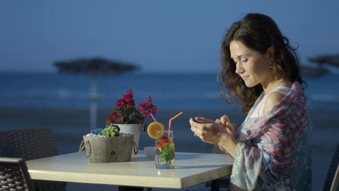 Happy beautiful woman chatting online on smartphone, vacation at seaside Footage