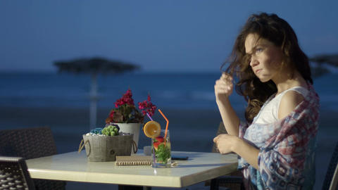 Thoughtful pretty female enjoying cocktail at seaside restaurant, romantic mood Footage