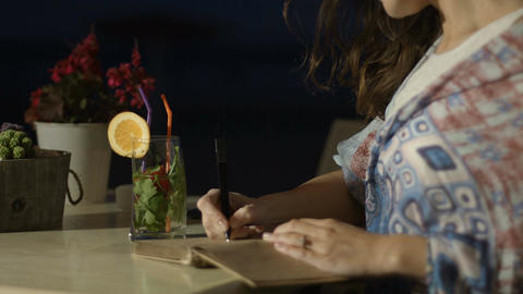 Hands of inspired woman writing poetry in notepad at outdoor restaurant at night Footage