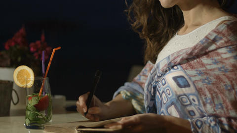 Closeup of happy and inspired pretty woman writing in diary with smile on face Footage