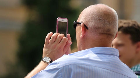 Senior man using smartphone with touchscreen to take photo, modern technologies Footage