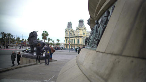 Tourists viewing bronze lion sculpture at Columbus Monument base in Barcelona Footage
